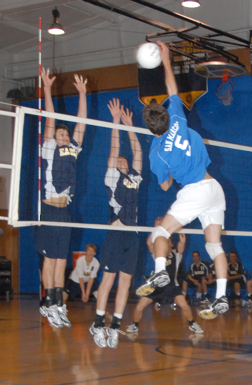 Jackson Kunz of San Marcos soars to pound a ball through an Arroyo Grande block. (Photo by Michael Holliday)