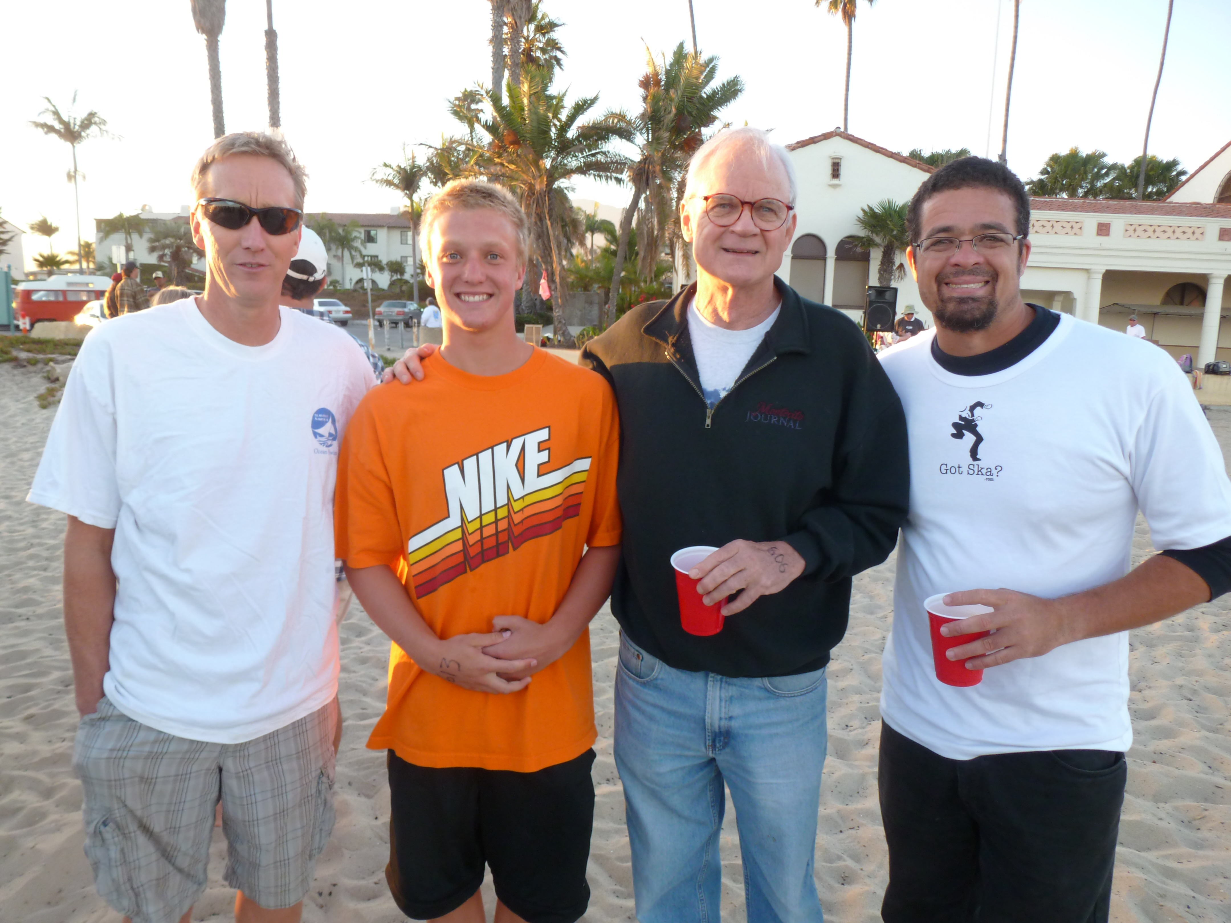 Reef & Run ocean-swim winners Jon Clark (mile), Grant Schroeder (1k) hang out with 1960 Olympic gold medalist Jeff Farrell and his son, Marco, at East Beach.