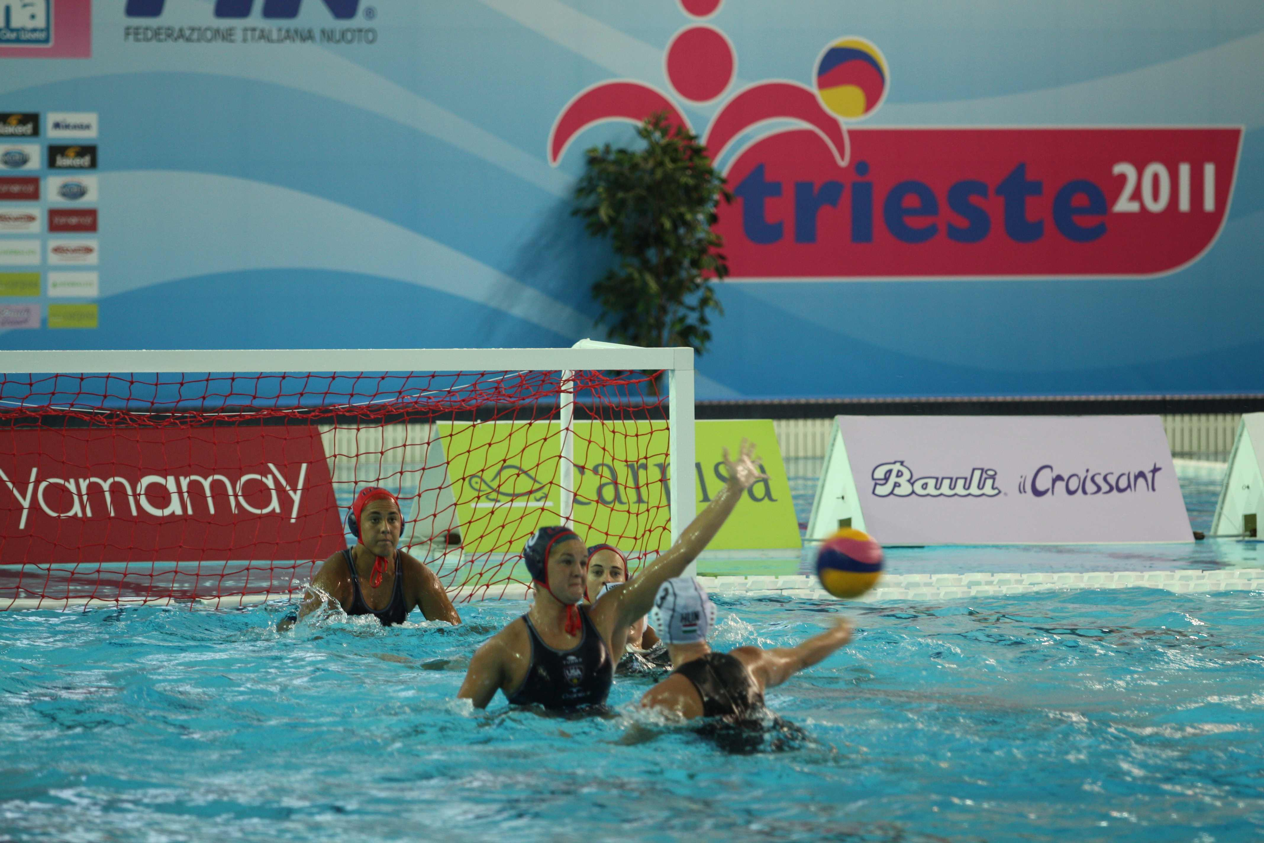 KIley Neushul defends against a Hungary shooter in front of goalie Sami Hill during quarterfinal action at the FINA Women's Junior World Championships. (Photo by Peter Neushul)