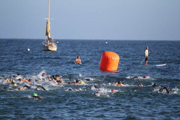 Swimmers in the 1K and 1-mile swim take off for the first buoy as two paddle boarders watch the competition.