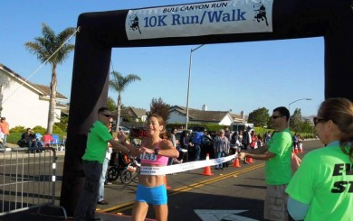 Joy Moats crossing the tape in Bull Canyon course record breaking 10K time
