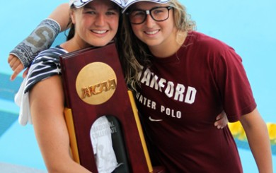 Sisters Kiley Neushul, left, and Jamie Neushul pose with the NCAA Championship trophy.